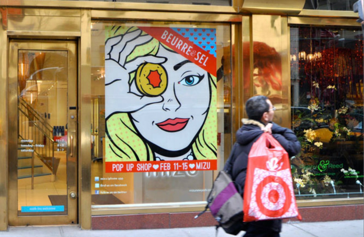 Printed window graphic of a cartoon woman drawn in a retro style, who appears to be looking at a pedestrian.